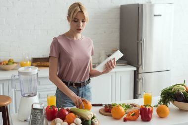 attractive vegan girl cooking and holding tablet with recipe in kitchen