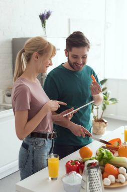 couple of vegans using tablet with recipe for preparing food at kitchen