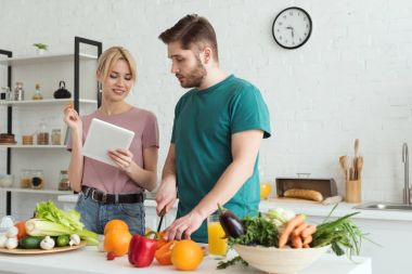 Couple of vegans using tablet with recipe for cooking at kitchen stock vector