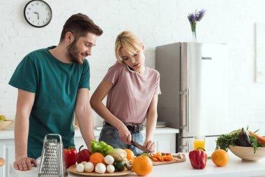 vegan girlfriend talking by smartphone while preparing meal at kitchen