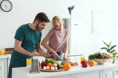 boyfriend grimacing while girlfriend cooking and talking by smartphone at kitchen