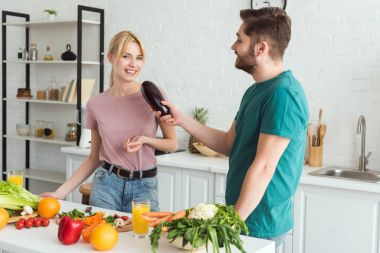 boyfriend using eggplant as microphone and having fun at kitchen, vegan concept