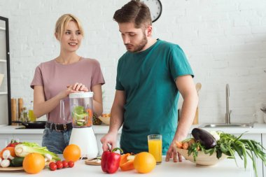 couple of vegans preparing vegetable juice with juicer at kitchen