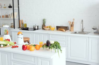 Interior of white modern kitchen with fruits and vegetables on kitchen counter stock vector