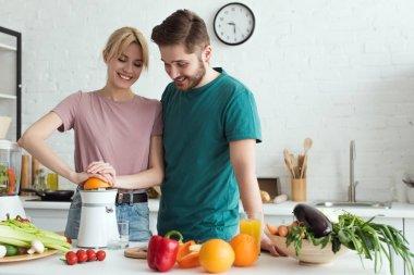 couple of vegans preparing fresh juice at kitchen