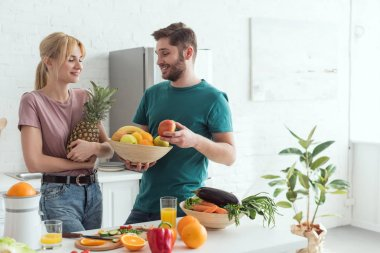 young vegan couple with fresh fruits and vegetables in kitchen at home