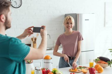 partial view of man taking picture of smiling girlfriend cooking in kitchen at home, vegan lifestyle concept