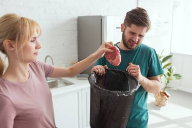 couple throwing away raw meat in kitchen at home, vegan lifestyle concept