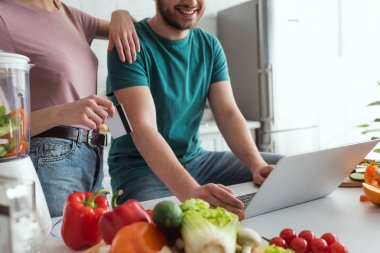 partial view of vegan couple with laptop shopping online in kitchen at home
