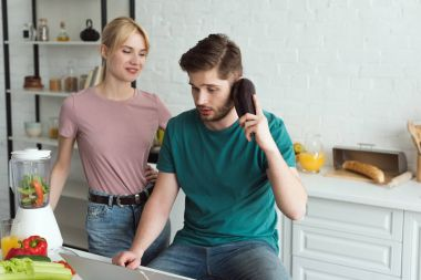 man pretending talking on eggplant at table with laptop and girlfriend near by in kitchen at home, vegan lifestyle concept