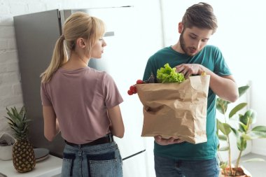 vegan couple with paper bag full of fresh vegetables in kitchen at home