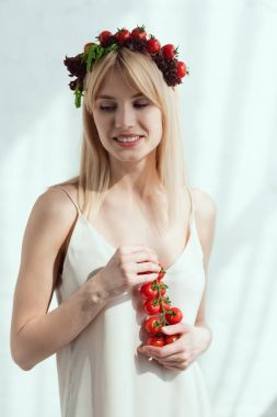 smiling woman with cherry tomatoes in hands and wreath made of fresh lettuce and cherry tomatoes, vegan lifestyle concept