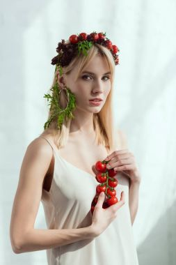 young woman with cherry tomatoes in hands and earring made of fresh arugula, vegan lifestyle concept