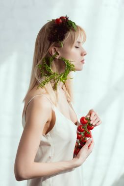 side view of young woman with cherry tomatoes in hands, wreath made of fresh vegetables and earring made of fresh arugula, vegan lifestyle concept