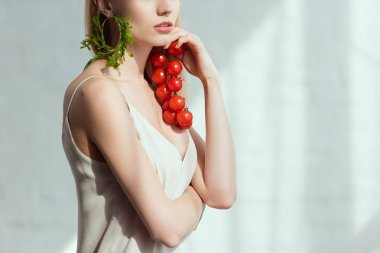 partial view of woman with cherry tomatoes in hand and earring made of fresh arugula, vegan lifestyle concept