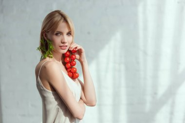 young woman with cherry tomatoes in hand and earring made of fresh arugula, vegan lifestyle concept