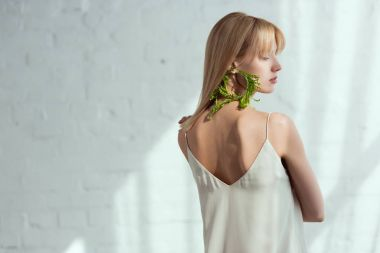 back view of young woman in dress with earring made of fresh arugula, vegan lifestyle concept