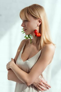 attractive woman in dress with earrings made of fresh arugula and cherry tomatoes, vegan lifestyle concept