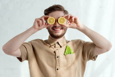 obscured view of smiling man with lemon pieces and savoy cabbage leaf in pocket, vegan lifestyle concept