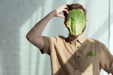 obscured view of pensive man with savoy cabbage leaf on face, vegan lifestyle concept