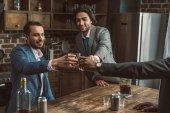 oříznutý snímek šťastné mužských přátel cinkání sklenic whisky, zatímco párty společně