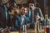 Veselá mnohonárodnostní muži v oblecích pomocí smartphone a společně pití alkoholických nápojů