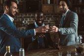 Fotografia giovani amici allegri del maschi in giacca e cravatta che clinking i vetri di whisky