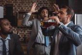 mnohonárodnostní podnikatelé při pohledu na přítele pití alkoholických nápojů z láhve