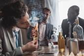 Fotografie junge Unternehmer halten Dollar Banknote und Rauchende Zigarre beim Feiern mit Freunden