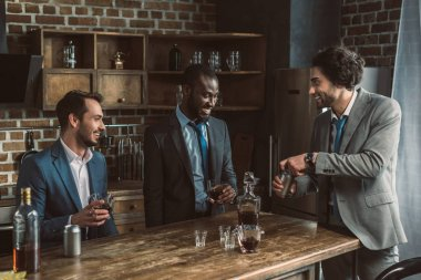 three young multiethnic businessmen drinking alcoholic beverages and partying together
