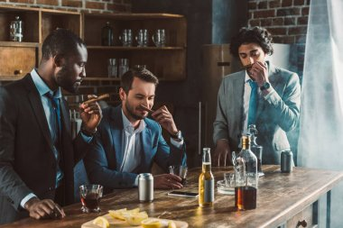 handsome young multiethnic men in suits holding cigars while partying together