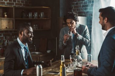 smiling young male friends in formal wear smoking cigars and drinking alcoholic beverages while partying together