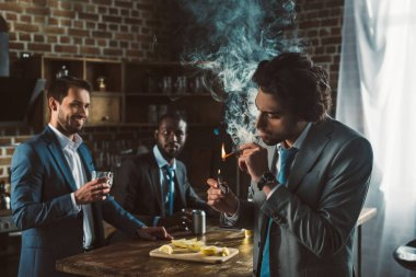 young man in suit smoking cigar and multiethnic friends drinking alcoholic beverages behind