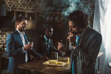 handsome young businessman smoking cigar while smiling friends drinking alcohol beverages behind