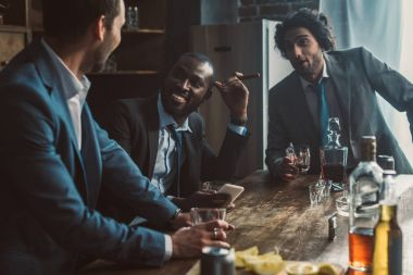 smiling multiethnic men talking, drinking whiskey and smoking cigars while partying together