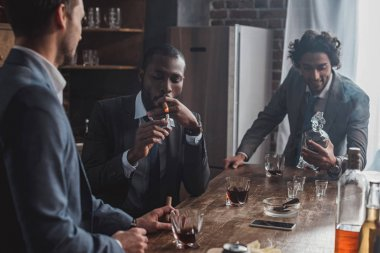 three multiethnic men in suits smoking cigars and drinking alcohol together