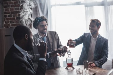 three smiling multiethnic businessmen smoking cigars and clinking glasses of whiskey