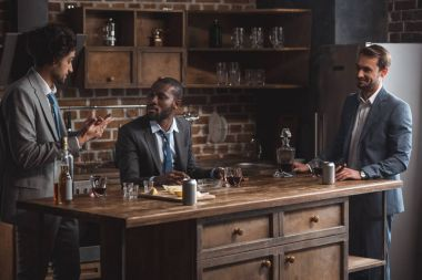 three multiethnic male friends in suits talking while drinking alcohol together