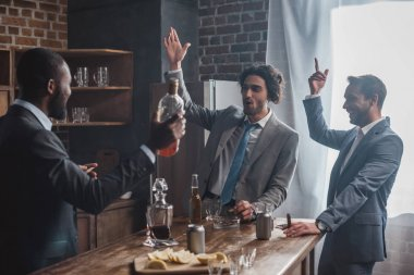 excited multiethnic businessmen smoking cigars and drinking whisky