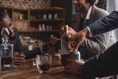 cropped shot of multiethnic men in suits drinking alcoholic beverages together