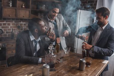 young multiethnic businessmen smoking cigars and drinking alcoholic beverages