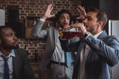 multiethnic businessmen looking at friend drinking alcohol beverages from bottles