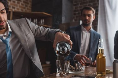 cropped shot of man in suit pouring whiskey while friend standing behind