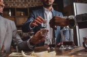 Fotografie Oříznout záběr mnohonárodnostní mužů dohromady pití alkoholu
