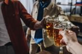 oříznutý snímek mužských přátel cinkání sklenic piva