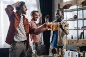 vzrušený mužských přátel cinkání pivní sklenice, zatímco párty společně