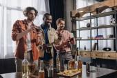 usmívající se mnohonárodnostní muži hrají s joysticky a párty společně