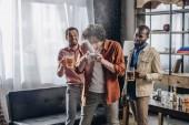 Fotografia multietnici amici guardando uomo che beve birra dalla latta di risata
