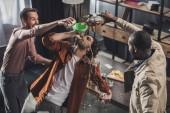 Fotografia vista di alto angolo delluomo che beve da imbuto mentre amici versando bevande alcoliche