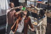 Fotografia vista di alto angolo delluomo che beve da imbuto mentre amici versando bevande alcoliche da bottiglie di vetro e lattine